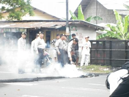 terlihat seorang polisi sedang berusaha untuk memadamkan api dari ban mobil yang dibakar pendemo