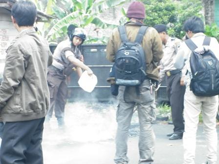 terlihat seorang polisi yang sedang berusaha memadamkan api yang langsung didekati para wartawan untuk diambil gambarnya