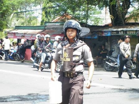 seorang polisi dengan perlengkapan alat pemadam kebakaran berada dibagian depan tubuhnya